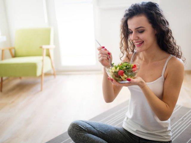Mujer-joven-sentada-en-un-sillon-comiendo-ensalada-de-vegetales