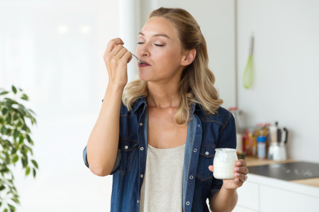 joven-bella-mujer-comiendo-yogur-casa_1301-7452